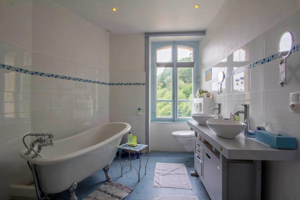 Spacieuse salle de bain (10m2) de la chambre Duc de Rohan, côté Est. Elle donne sur le parking et le jardin de la maison