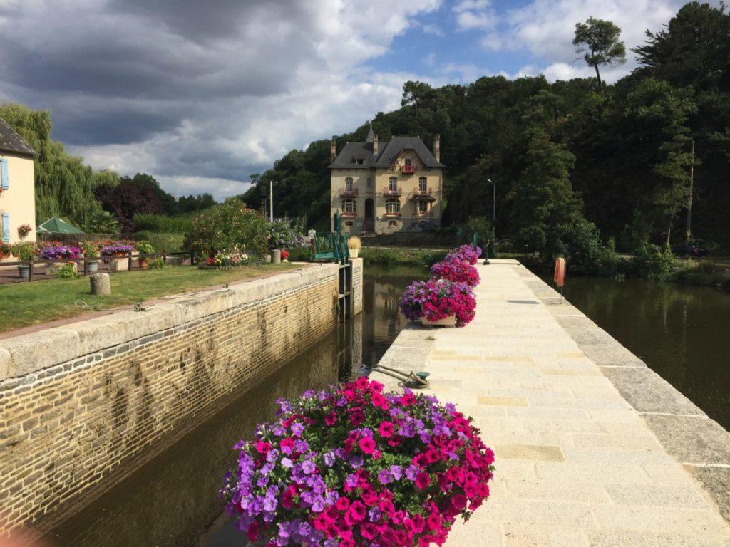 Prise de vue depuis l'écluse avec la rangée de pétunia.Villa Tranquillité, sur le canal de Nantes à Brest à Rohan
