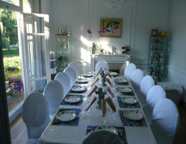 La table d'hôtes est servie dans le salon avec vue sur le canal et l'écluse