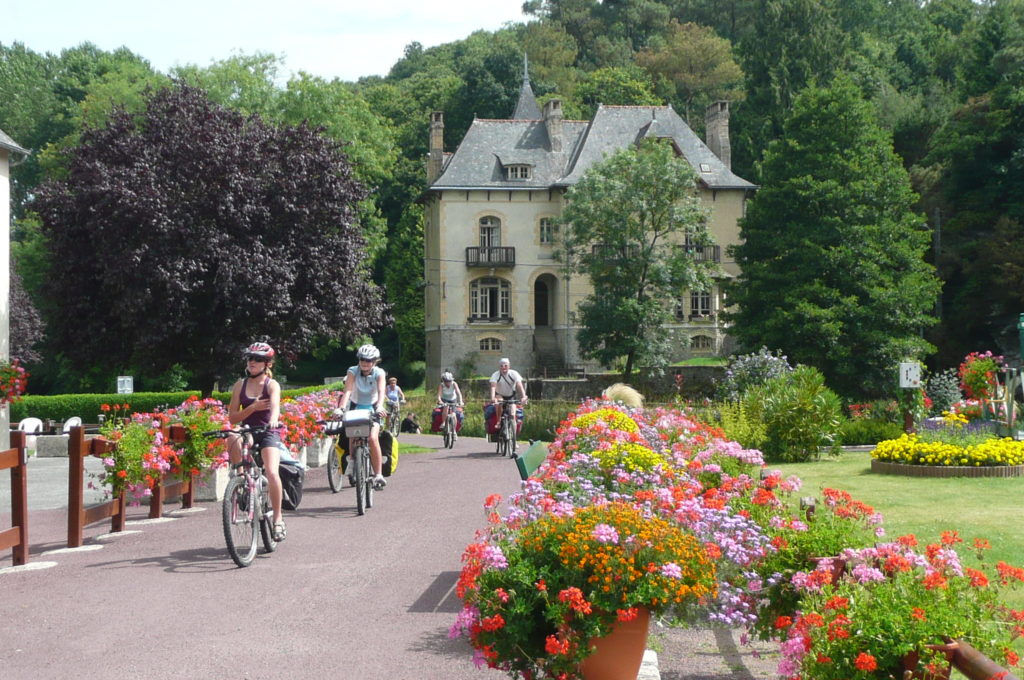 Un groupe de vélo arrive par le hallage devant la Villa Tranquillité